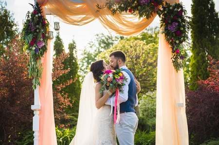 Happy couple kissing under the textile arch with flowers outdoors