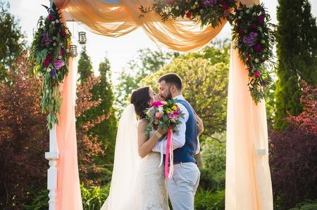 Glückliches Paar, das draußen unter dem Textilbogen mit Blumen küsst
