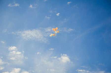 Batch of air balloons was laucnhed fly away from the event. Ten balloons peach color flying in the blue sky.