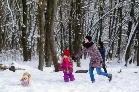 Family run in snow after their dog with purple toy