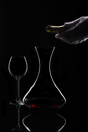 Red wine decanting process at isolated black