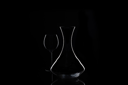Decanter and wine glass at black isolated background