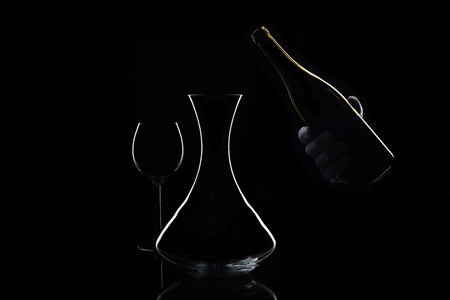 Hand in white glove holds bottle of wine and decanter Stock Photo