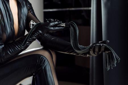 Gants et fouet en cuir noir avec frange et poignée. Maîtresse avec un fouet dans la chambre.