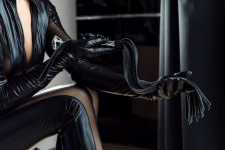 Black leather gloves and whip with fringe and handle. Mistress with a whip in room.