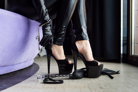 Woman in total leather black with sexy accessories. High heels, handcuffs and crop whip close-up.
