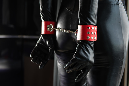 Female ass and hands with leather cuffs and chains on wrists 스톡 콘텐츠
