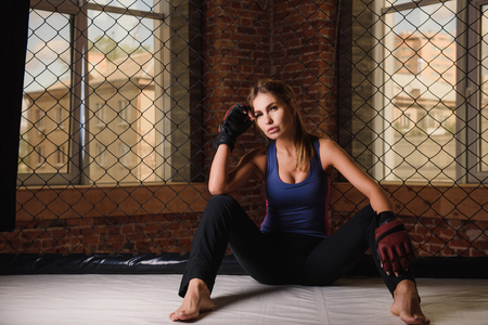 Sexy woman sitting at gym floor