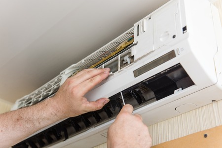 Master check and clean air conditioning Foto de archivo