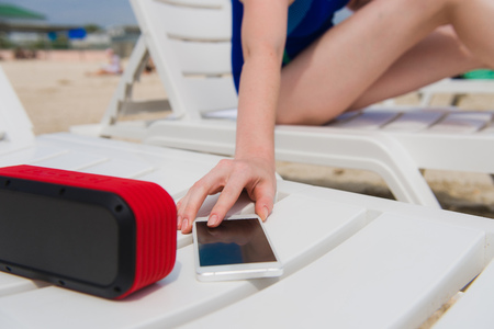 Female hand with phone and speaker at beach Banco de Imagens