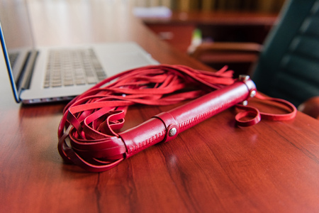Red leather whip on table with laptop Stock Photo