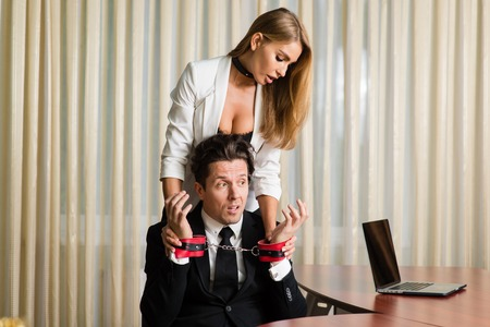 Sexy blonde female put handcuffs on boss