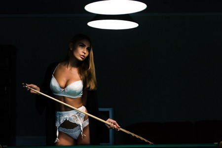 Sexy woman with billiard cue