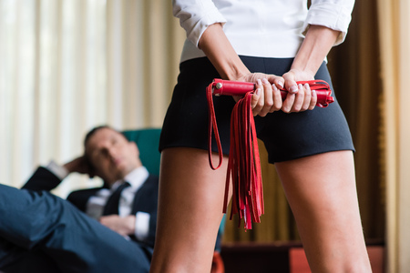 Woman hold leather red whip behind back