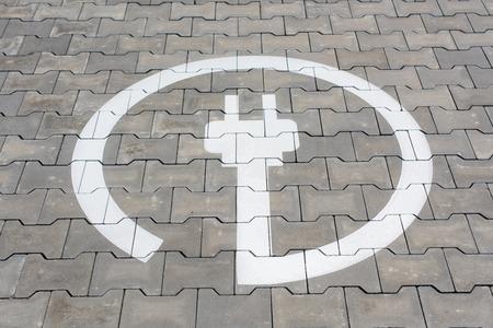 Símbolo de la estación eléctrica para coches eléctricos en la zona de aparcamiento