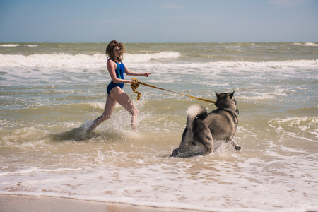 Woman with husky dog at beach