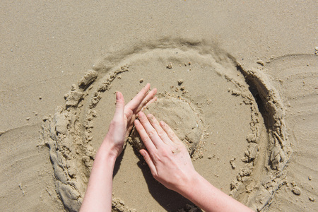 women's hands do a sand castle on the beach. view from above 免版税图像