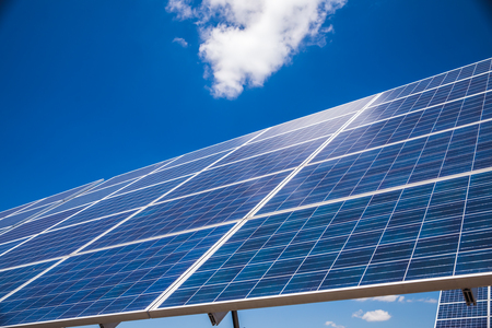 Group of solar panels on a blue sky with clouds