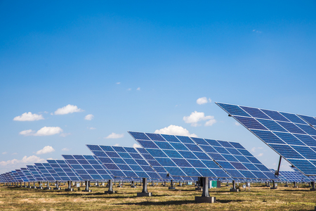 Group of solar panels on a blue sky with clouds. Concept of solar energy. Side view. Stock Photo