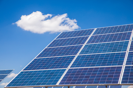 Close-up of a photovoltaic solar power plant against blue sky with clouds Stock Photo