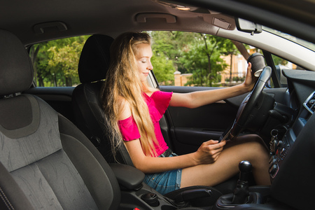 Young girl driver with tablet in car