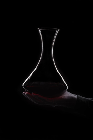 Hand of man holds decanter with red wine Stock Photo