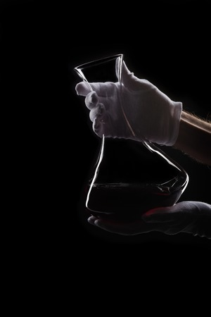 Male hand in white gloves with decanter