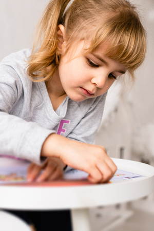 Small girl with coloring book and pencils Stock Photo