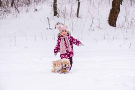 Toddler smiling girl play with dog during winter Stock Photo