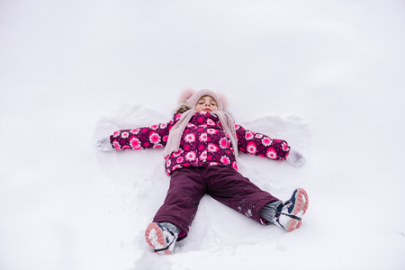 Toddler girl in pink male snow angel
