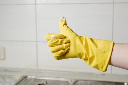 Mano femminile in guanto giallo che mostra pollice in su