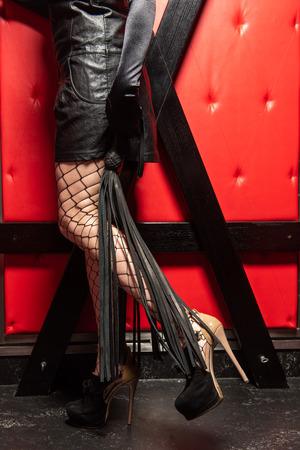 Femme de beauté avec fouet en robe de cuir. Banque d'images