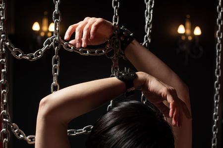 Handen van vrouw in handboeien tussen kettingen in het donker