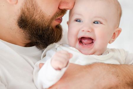 Glückliches Baby in den Armen des jungen Vaters Standard-Bild