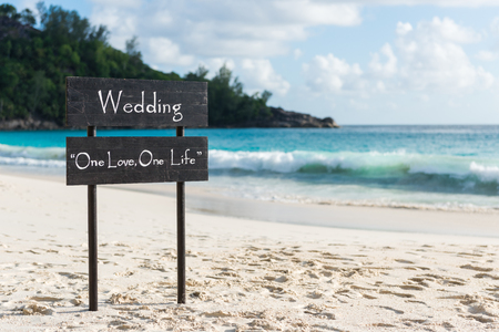Black wooden plate with wedding sign at tropical beach