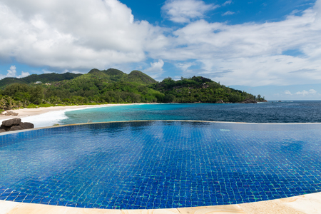 Round infinity swimming pool with ocean view. Beautiful view at Seychelles island.