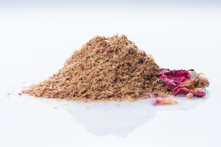 Adwiya. Close-up of persian spices blend with Rose on white background