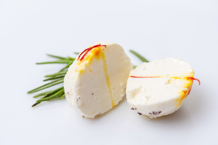 Two halves of cheese ball with sprig of thyme on white background.