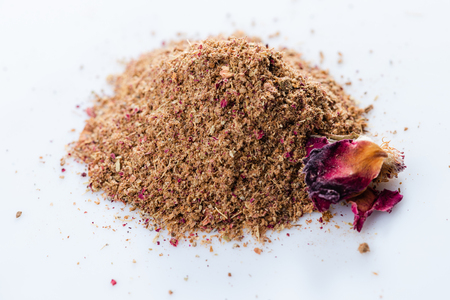 Adwiya. Close-up of persian spices blend with Rose on white background. View from above.