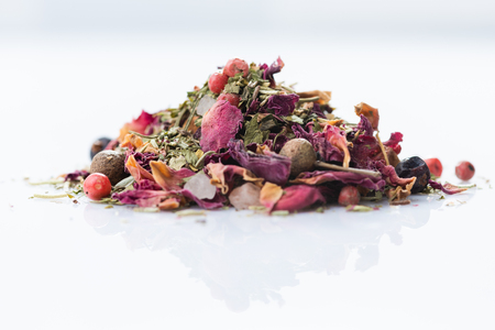 Close-up of italian spices blend with rose on white background