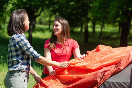 Smiling brunette women with tent carcass sticks