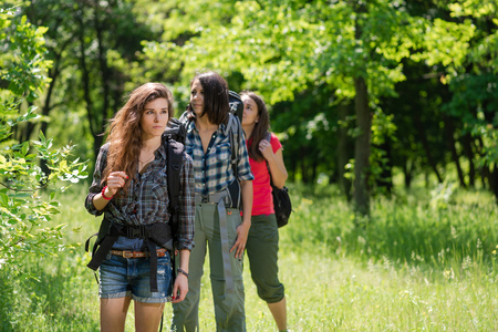 Three female tourists in forest with backpacks