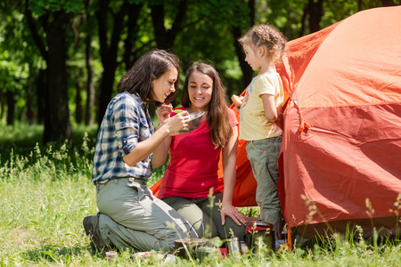 Three tourist females eat near tent outdoors