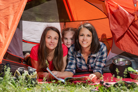 Two women and child at camping tent