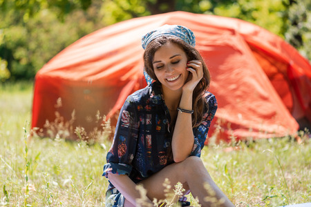 Portrait of young tourist girl sit near tent