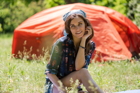 Portrait of tourist girl sit near tent