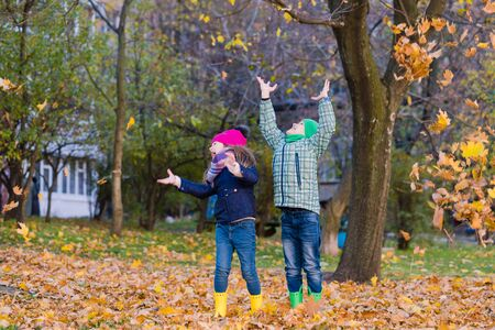 Two smilling children play with maple leaves in park. Boy and girl stare at falling leaves. Stock Photo