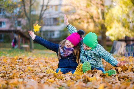 Cute kids hugs and sit in autumn leaves