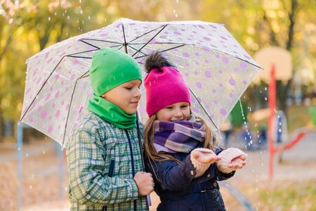 Preteen boy and girl walk in rainy park outdoors Stok Fotoğraf