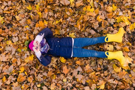 Preteen girl lay at leaves and show heart